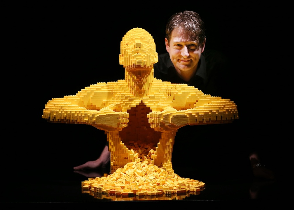 Artist Nathan Sawaya stands with his sculpture 'Yellow' at the Art of Brick Exhibition in London