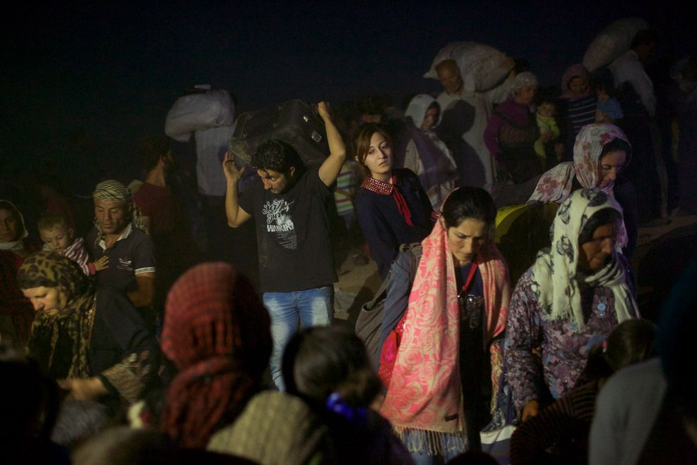 Thousands of Syrians from Kobani pour into Turkey on Friday evening. Turkish military personnel cut a hole into the barbed wire fence to allow the thousands of Syrian Kurds to seek safety